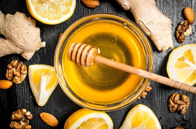 Honing achtergrond. verse honing met gember en citroen. op een zwart bord.