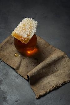 Honing achtergrond. zoete honing in de kam en glazen pot. donkere achtergrond.