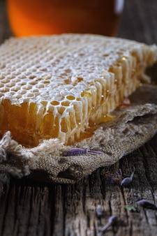 Honing achtergrond. zoete honing in de kam, glazen pot. op houten achtergrond