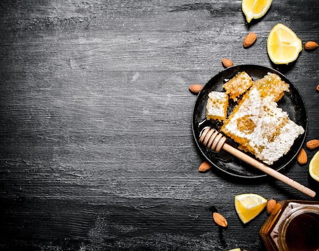Honing achtergrond zoete natuurlijke honing met citroen op zwarte rustieke achtergrond