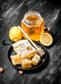 Honing achtergrondstijl verse zoete honing met citroen op zwarte rustieke achtergrond