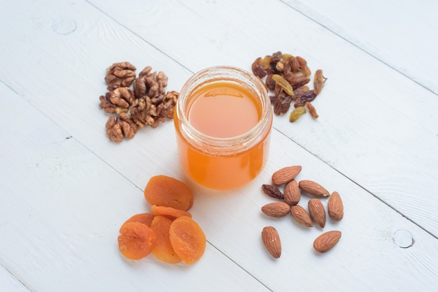 Honing, amandelen, walnoten en gedroogde abrikozen. gedroogde vruchten liggend op een witte houten tafel.