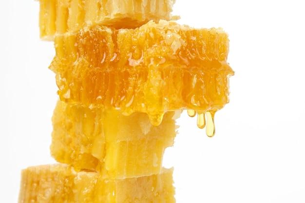 Honing die uit de honingraten stroomt op een lichte achtergrond
