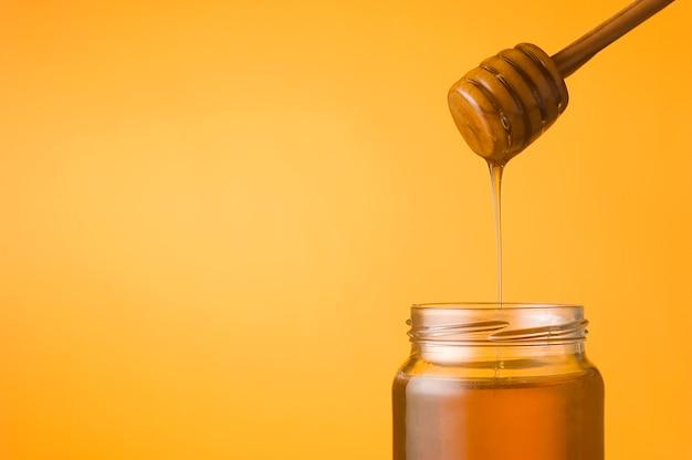 Honing die van een beer in een pot op oranje achtergrond valt. ruimte voor tekst