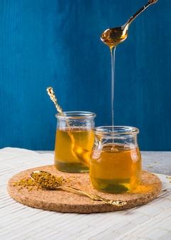 Honing druipend van lepel in pot en bijenpollen over cork onderlegger voor glazen