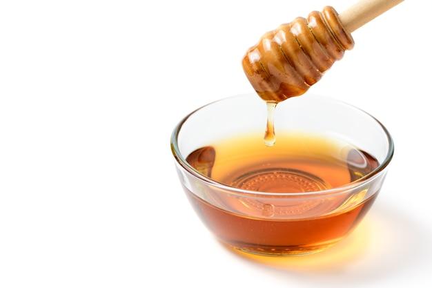 Honing druipt van de lepel in de glazen kom geïsoleerd op een witte muur met kopie ruimte
