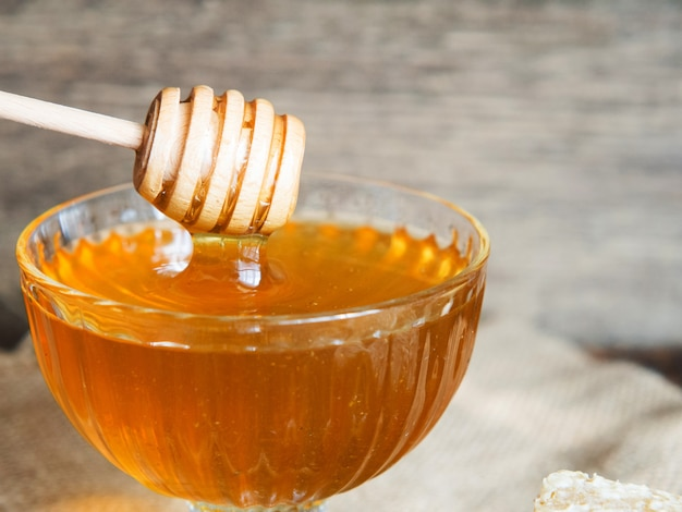 Honing druipt van een honingdipper in een mooie glazen kom. detailopname. gezonde biologische dikke honing en kammen.