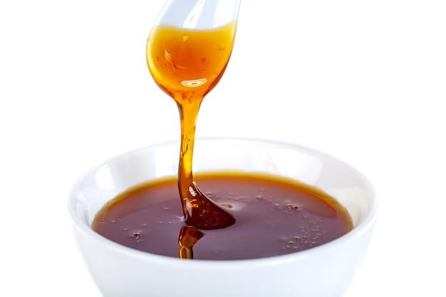 Honing druipt van keramische lepel tot keramische kom, eten