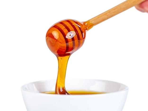 Honing druipt van woodin dipper tot keramische kom, eten