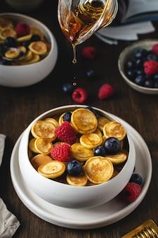 Honing druppels gieten over plaat met pannenkoek granen, trendy mini pannenkoeken met frambozen, bosbessen op houten tafel