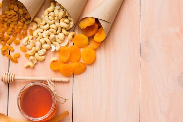 Honing en gedroogd fruit op een houten tafel.