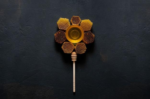 Honing en honingraat in de vorm van een bloem op zwarte tafel