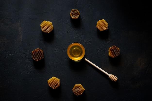 Honing en honingraat in de vorm van een klok op zwarte tafel