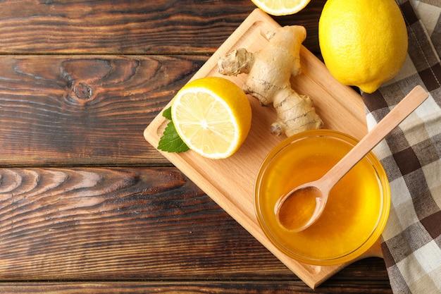 Honing, gember, citroenen en handdoek op houten achtergrond