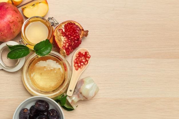 Honing, granaatappel, appel en dadels op een houten bord. joods nieuwjaar rosj hasjana viering