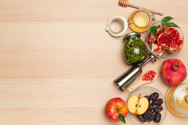 Honing, granaatappel, appel en dadels op houten bord.