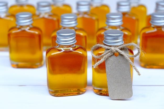 Honing in de glazen flessen voor huwelijksgeschenk met bruine tag.