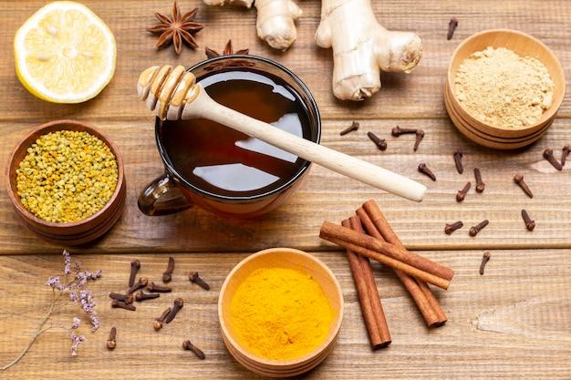Honing in een glazen kom. bloemstuifmeel, droge gember en kurkumapoeder in houten kommen. houten achtergrond. bovenaanzicht
