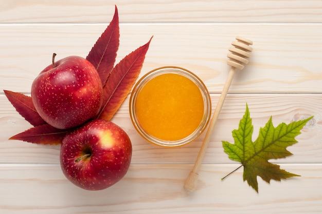 Honing in een glazen pot en rode appels op een witte houten