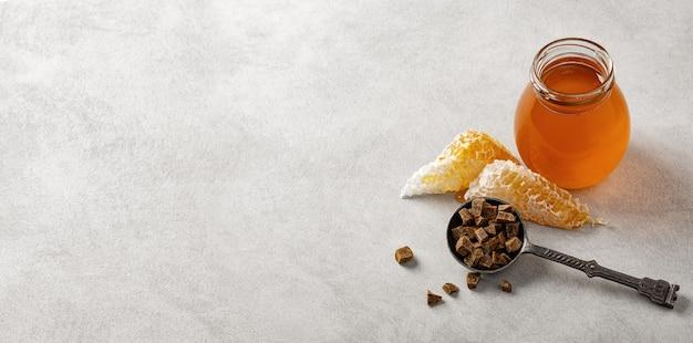 Honing in een glazen pot, honingraat en propolis in een ijzeren lepel.