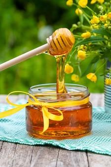 Honing in een glazen pot met bloemen