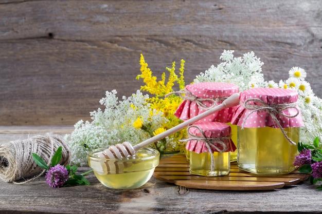 Honing in een glazen potten, en honing beer op een rustieke houten tafel