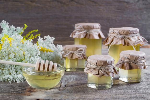 Honing in een glazen potten, wilde bloemen op een rustieke houten tafel