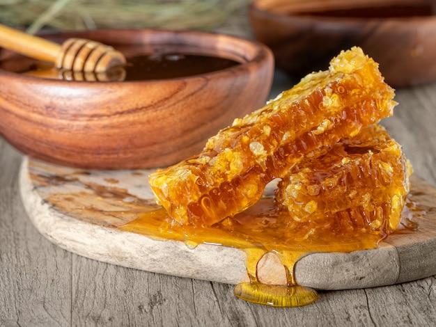 Honing in een houten kom en een honingraat op tafel. rustieke stijl