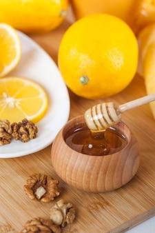 Honing in een houten kom met honing beer en citroen op een houten keukenbord.