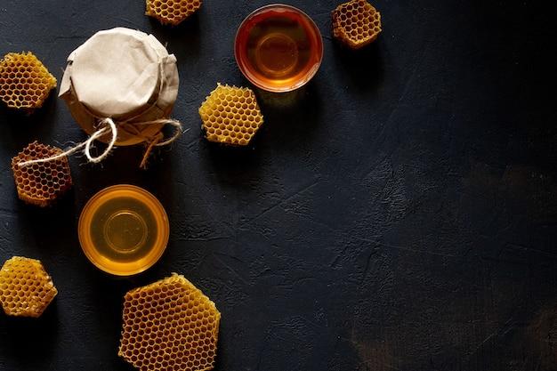 Honing in een pot en een honingraat. op een zwarte houten achtergrond. bovenaanzicht.