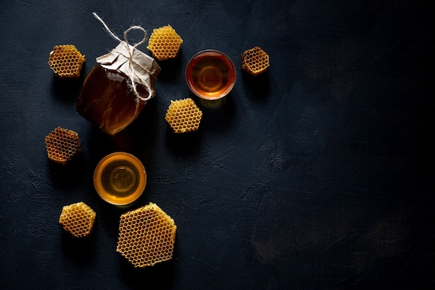 Honing in een pot en een honingraat. op een zwarte houten achtergrond. vrije ruimte voor tekst. bovenaanzicht.