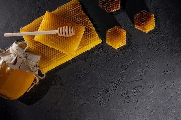 Honing in een pot en een honingraat. op een zwarte houten achtergrond. vrije ruimte voor tekst. bovenaanzicht