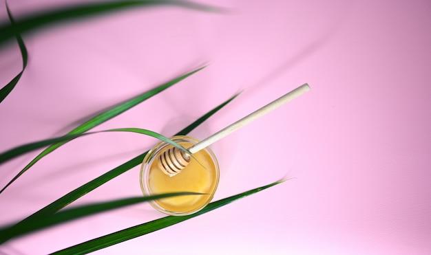 Honing in een pot op roze achtergrond
