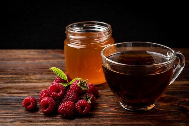 Honing in glazen pot en verse frambozen op donkere houten achtergrond.