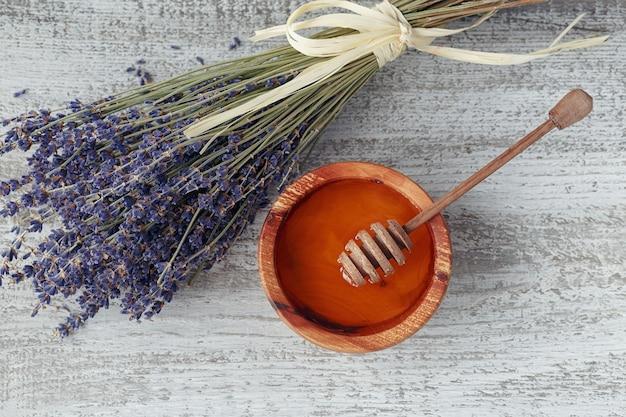 Honing in houten kom met honing dipper en lavendel bloemen op witte vintage houten achtergrond. bovenaanzicht.