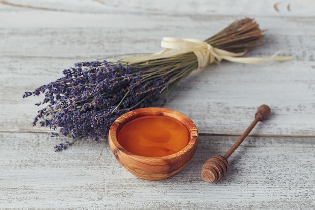 Honing in houten kom met honingdipper en lavendelbloemen op witte uitstekende houten achtergrond