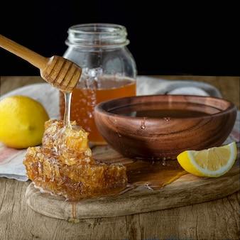 Honing in pot met honingraat en houten drizzler met citroen op houten tafel. donkere achtergrond