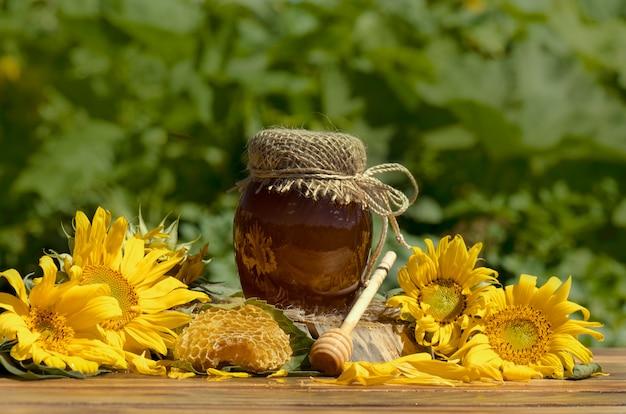 Honing in pot met honingsdipper op rustieke houten lijst. zoete honing in de kam. gezonde voeding concept. honingproducten door biologische ingrediënten.