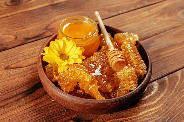 Honing in pot met honingsdipper op uitstekende houten achtergrond
