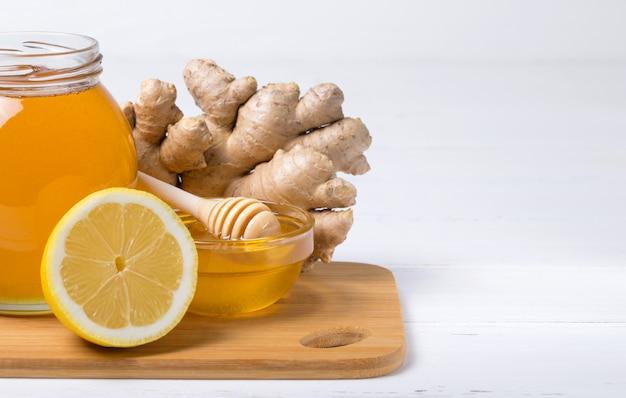 Honing met citroen op houten lijstachtergrond