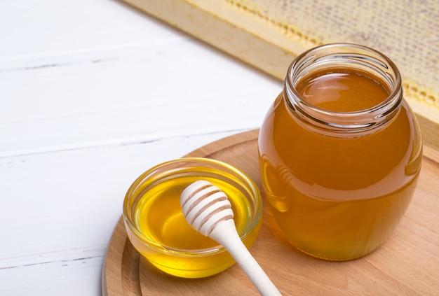 Honing met houten honingsdipper op houten lijst