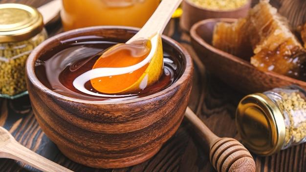 Honing met lepel over houten wallwith honingraat en propolis, vloeibare suikersiroop, bloemennectar