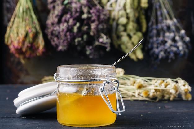 Honing met thee op rustieke lijstachtergrond met kruiden