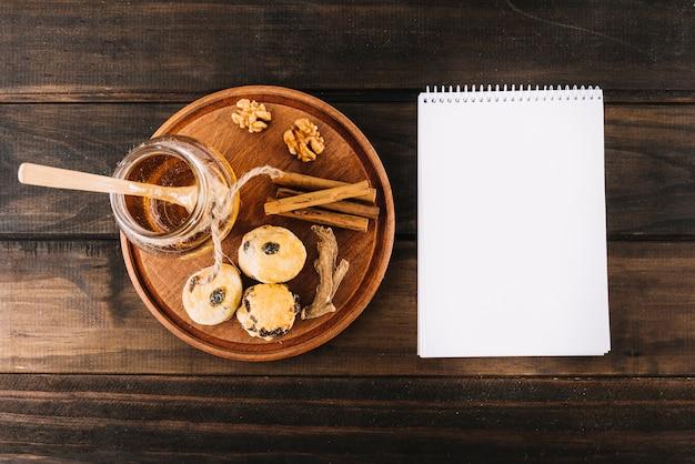 Honing; okkernoot; specerijen en cup taarten in de buurt van spiraal kladblok op houten oppervlak