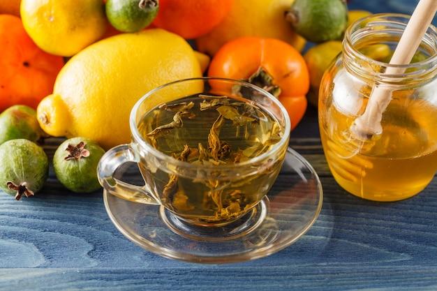 Honing pot en verse appels met granaatappel over blauwe tafel