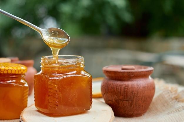 Honing stroomt van een stalen lepel in een glazen pot
