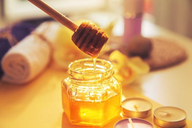 Honing wordt in de pot gegoten. spa zorgconcept. natuurlijke huidverzorging voor thuis. onscherpe achtergrond. mooi licht.