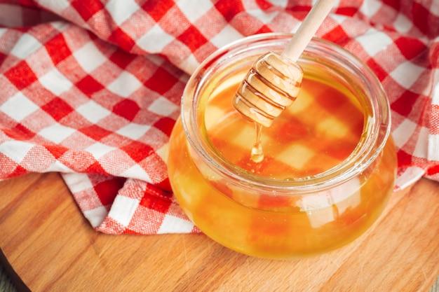 Honing. zoete honing in glazen pot op houten.