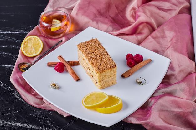 Honingcake met kaneel en fruit op wit bord naast roze tafelkleed.