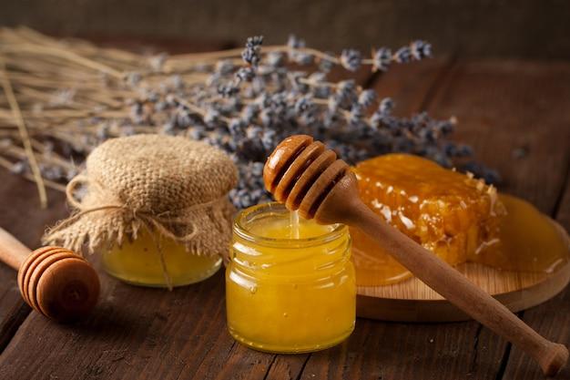 Honingdipper en honingraat. noten en appels met honing en verschillende soorten noten